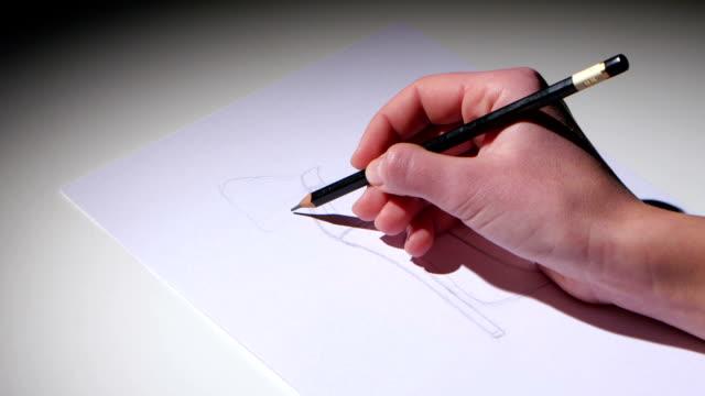 flickan sitter vid bordet och ritar en blyertsskiss av skon. närbild - endast flickor bildbanksvideor och videomaterial från bakom kulisserna