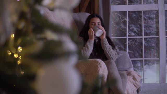 ein mädchen sitzt auf einem stuhl in der nähe der weihnachtsbaum und trinkt tee - cozy stock-videos und b-roll-filmmaterial