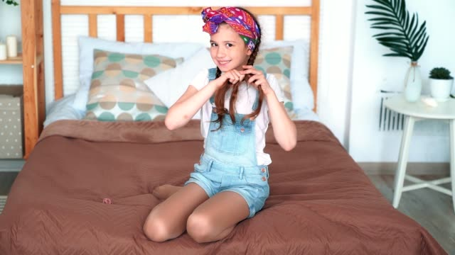 girl sits on bed, plaits her hair in braids, smile, looks at camera, slow motion - nastro per capelli video stock e b–roll