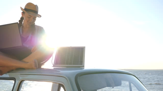 girl sits on car roof with solar array charges laptop and waving hello in backlight, summer season, female sitting on vintage car video