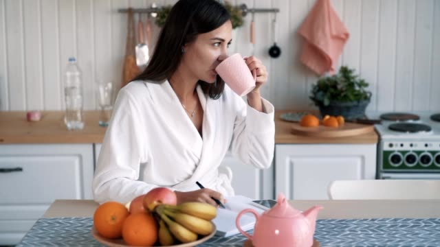 ragazza si siede in cucina, beve caffè e scrive per fare elenco in taccuino, rallentatore - to do list video stock e b–roll