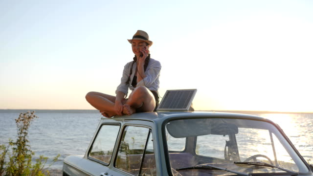 girl sits on retro car roof in backlight talking on cellphone and holds solar array, young woman using powered solar cell video