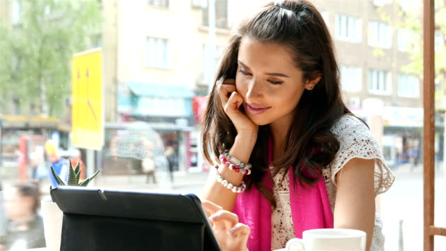 Girl sitting in a café and chatting on a tablet video
