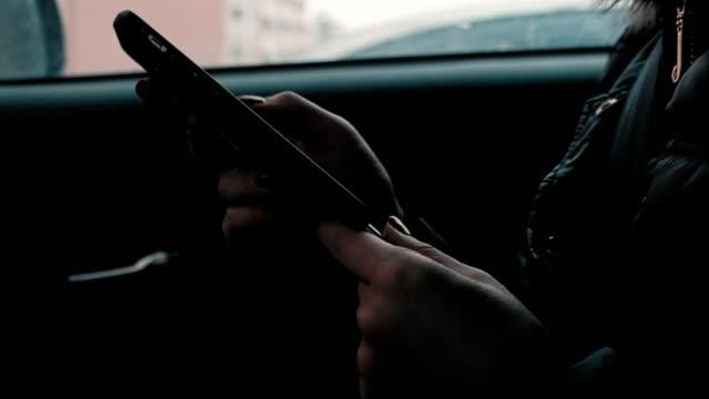 Una chica sentada en un auto y trabajando en el teléfono. El uso del teléfono - vídeo