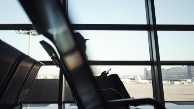 girl sitting in airport - табло вылетов и прилётов стоковые видео и кадры b-roll