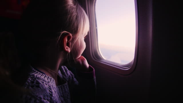 girl sitting in an airplane, looking out the window at the rising sun - sedili aereo video stock e b–roll