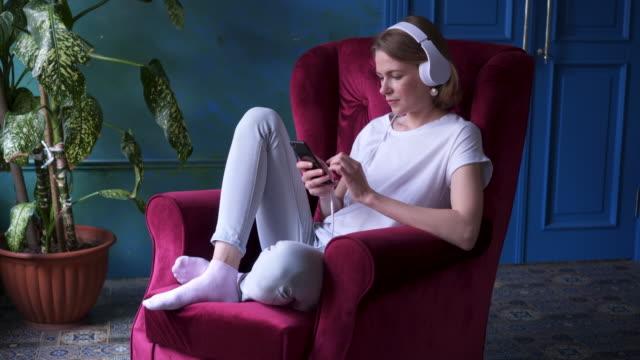 vidéos et rushes de jeune fille assise dans le fauteuil et écoute de la musique - podcasting