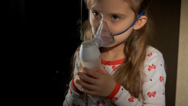 Girl sitting in bed in the hospital and inhales. The girl is sick, coughing, sad, not funny, treatment in the hospital, at the doctor's. Inhalation mask on her face. video
