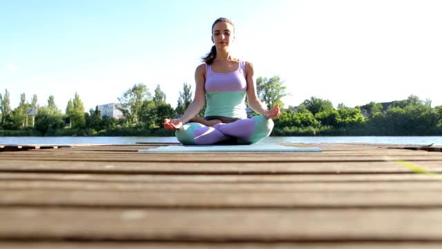 Mädchen sitzen in Lotus Pose auf einer Holzbrücke. Yoga – Video
