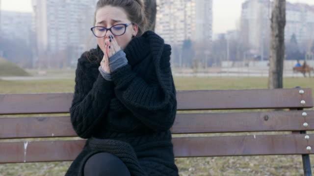vídeos y material grabado en eventos de stock de chica sentada en un banco del parque en el tiempo frío y tratando de calentar a sí misma - flu