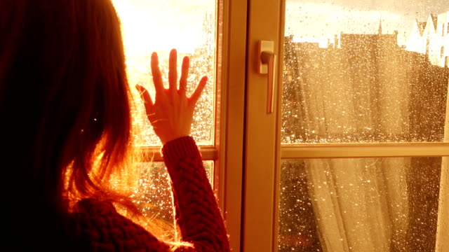 stockvideo's en b-roll-footage met meisje zittend op een vensterbank en kijken naar de avond stad aan de stralen van oranje zonsondergang zon - regen zon