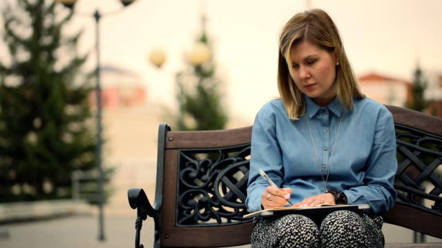 Girl sitting on a wooden bench, writes a notebook, outdoors video