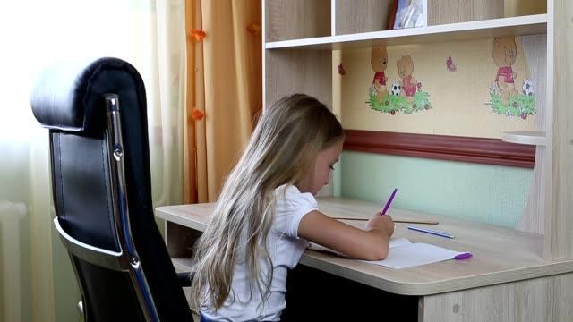 Chica sentada en la silla de cuero negro por mesa escribe algo en el notebook por pluma. - vídeo