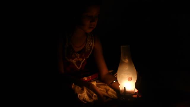 vídeos y material grabado en eventos de stock de chica sentada en la alfombra con lámpara - aldea