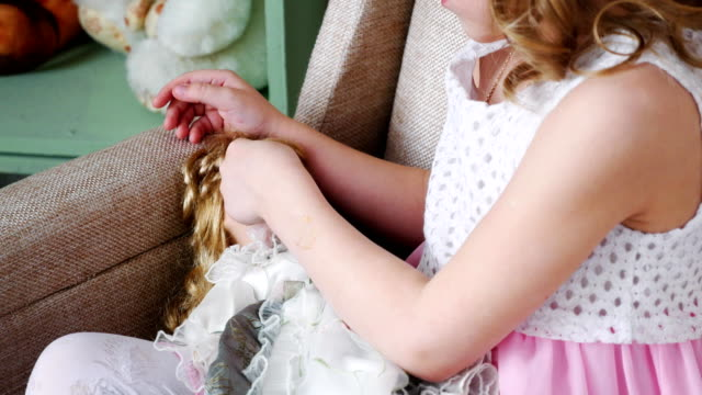girl sitting on chair and playing with a doll, close up. girl sitting on chair and playing with a doll, close up. doll stock videos & royalty-free footage