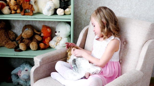 girl sitting on chair and playing with a doll. girl sitting on chair and playing with a doll. doll stock videos & royalty-free footage
