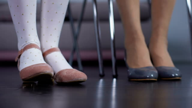 ragazza seduta sulla sedia vicino alla madre, calpestando le scarpe rosa giocosamente, coda d'attesa - scarpe video stock e b–roll