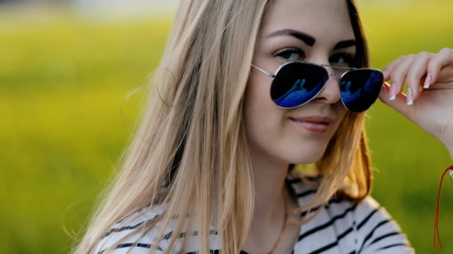 vídeos de stock e filmes b-roll de girl sitting on grass in sunglasses and winks to camera - piscar