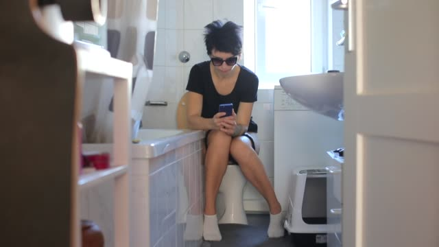 stockvideo's en b-roll-footage met meisje zittend op het toilet schrijft een bericht aan haar minnaar - cell phone toilet
