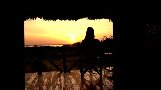 CLOSE UP: Girl sitting on wooden chair on veranda watching golden light sunrise CLOSE UP: Young girl relaxing after exciting safari trip and sitting on raised wooden deck in luxury glamping hut room in Lake Burunge Tented Camp admiring bushy landscape and amazing golden sunrise tanzania stock videos & royalty-free footage