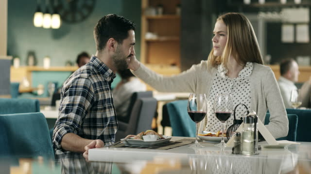 girl slap boyfriend over dinner in restaurant - lottare video stock e b–roll