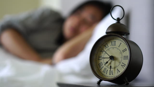girl sleeping on bed, clock on bedside table video