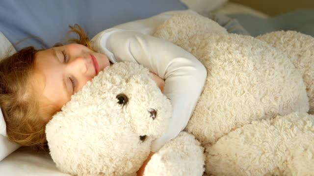 テディベア 4 k の寝室で寝ている女の子 - 4歳から5歳点の映像素材/bロール
