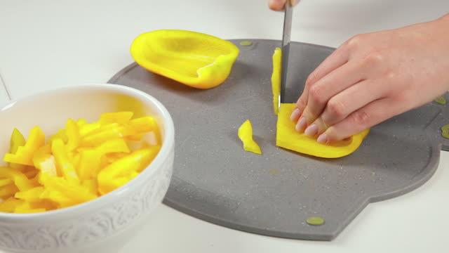 girl slices of yellow sweet pepper - ludzka kończyna filmów i materiałów b-roll