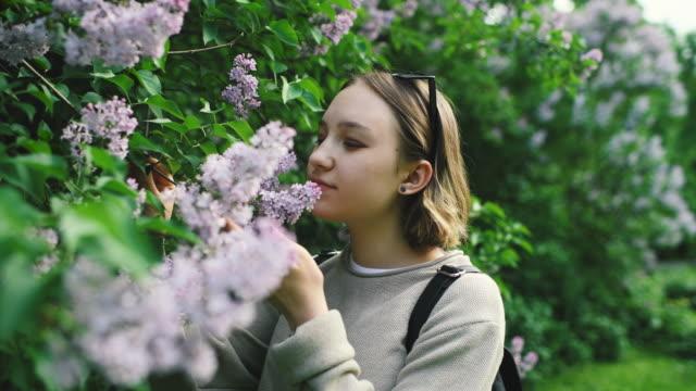 Girl smelling flowers in park in springtime