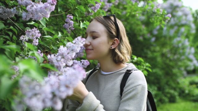 Girl smelling flowers in park in springtime