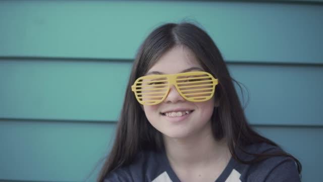 Une jeune fille souriante et porte des lunettes jaune nouveauté - Vidéo