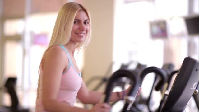 Girl smiling to camera during workout on orbitrek video