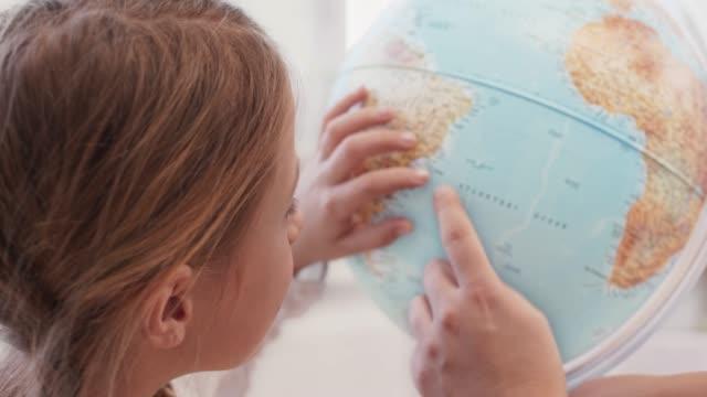 flicka leende när du använder globen på skriv bordet - bordsjordglob bildbanksvideor och videomaterial från bakom kulisserna