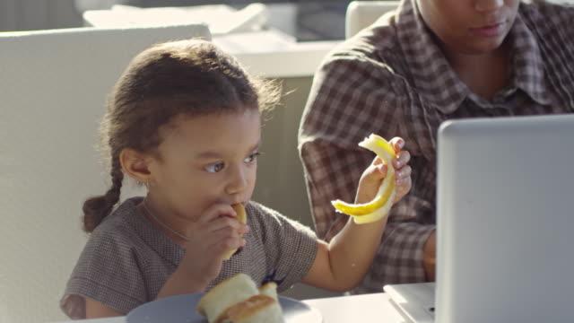 flicka snacking samtidigt spendera tid med arbetande mamma - working from home bildbanksvideor och videomaterial från bakom kulisserna