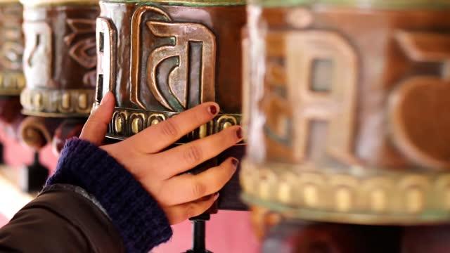 vídeos de stock e filmes b-roll de girl spinning buddhist monastery prayer wheels with hand close up clip - buda