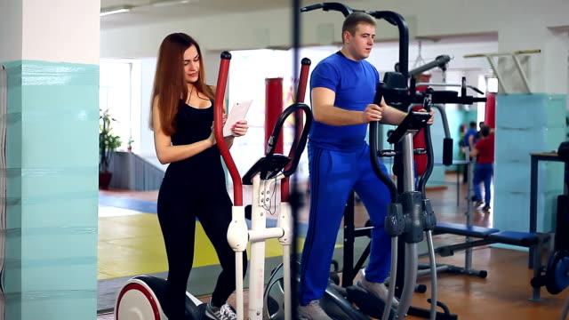 Girl sports man trainer ellipsoid on simulator  involved video