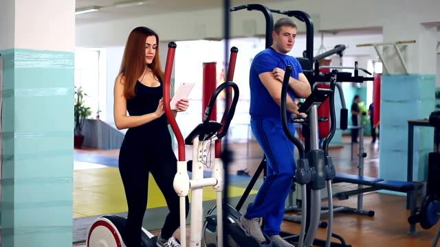 Girl sports trainer man ellipsoid on simulator  involved video