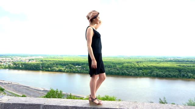 girl standing alone on a top of city and looking into the distance at the nature landscape video