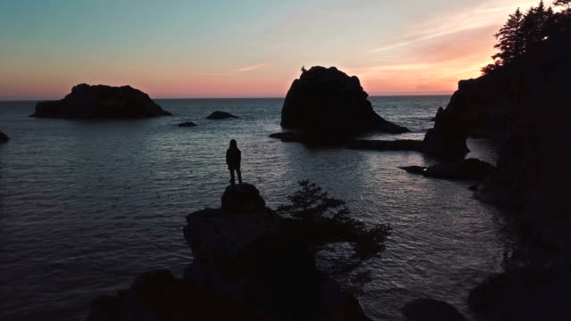 Girl stands on top of sea stack of Oregon coast watching twilight video