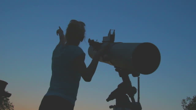 Girl stargazing with a telescope. video