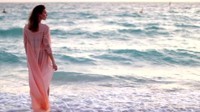 Jeune fille reste sur la plage proche mer - Vidéo