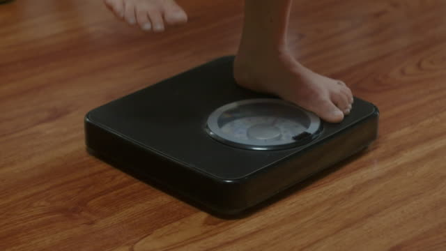 girl stepping on bathroom scales to check weight