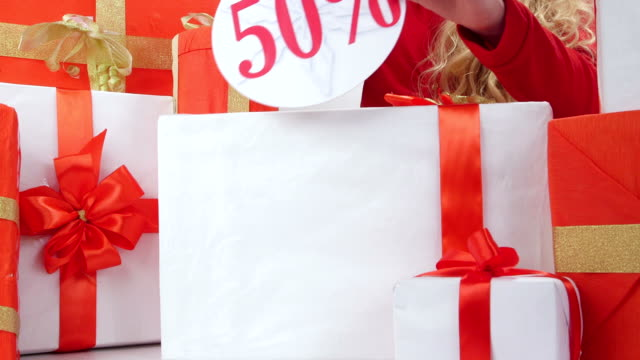 Girl sticks half price sign on red white gift boxes video