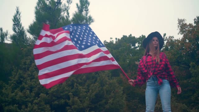 A girl straightens a cowboy hat and holds in her hand a large American flag. Patriotism concept
