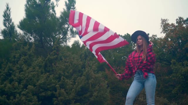 A girl straightens a cowboy hat and holds in her hand a large American flag. Video for America Independence Day