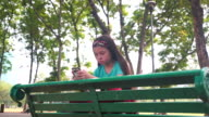 istock Girl strain using smart phone and sitting on chair in the park 1211458608