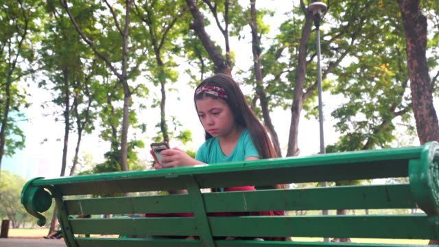 Girl strain using smart phone and sitting on chair in the park