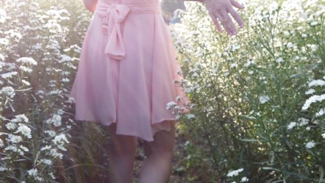 Girl stroll in daisy flower garden