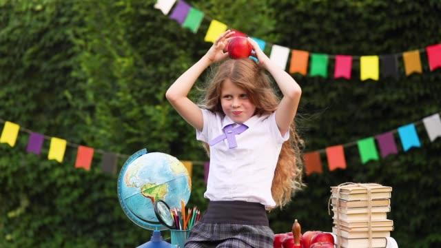 flicka student sitter på en skola skrivbord hålla ett äpple på huvudet - människorygg bildbanksvideor och videomaterial från bakom kulisserna