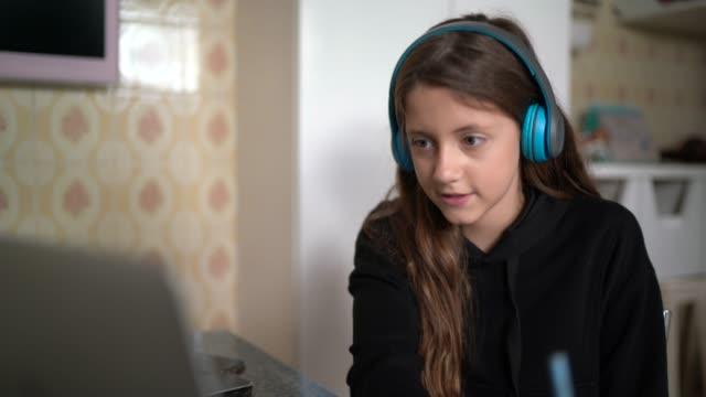girl studying and making a video call via laptop at home - odosobniony filmów i materiałów b-roll